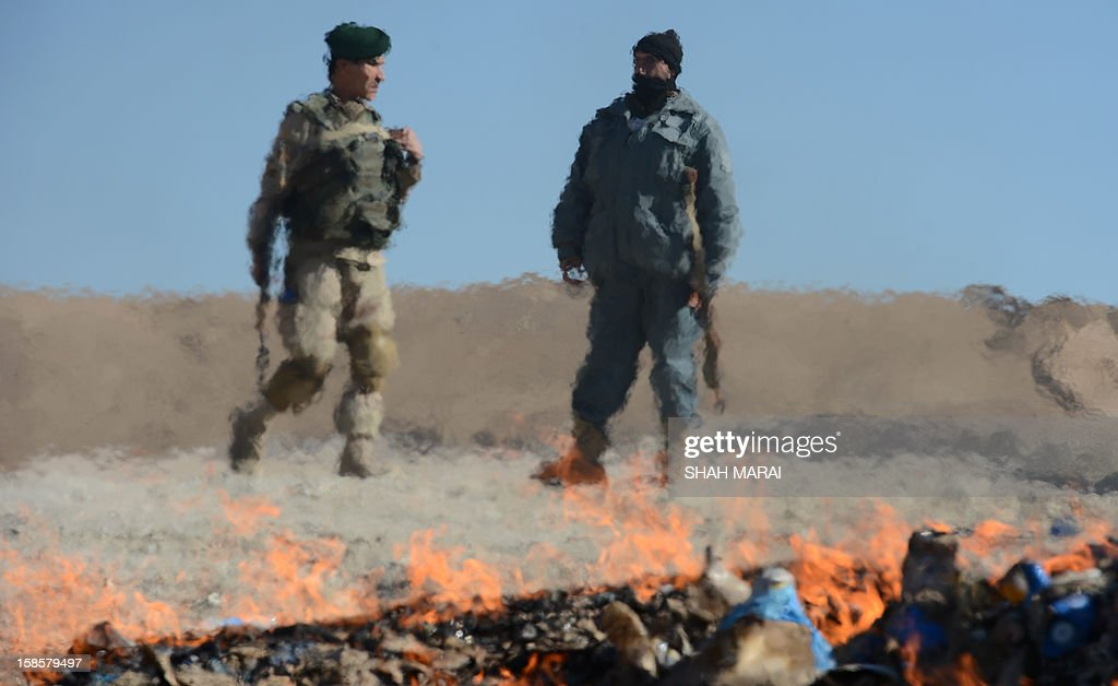 This photo taken on December 19, 2012 shows an Afghan policeman (R) and commando (L) standing guard as a pile of narcotics is burned by officials on the outskirts of Jalalabad Nangarhar province. The United Nations said in November that opium poppy cultivation in Afghanistan has increased by 18 percent this year, sending a 'serious alarm signal' from the world's biggest opium producer. AFP PHOTO / SHAH Marai