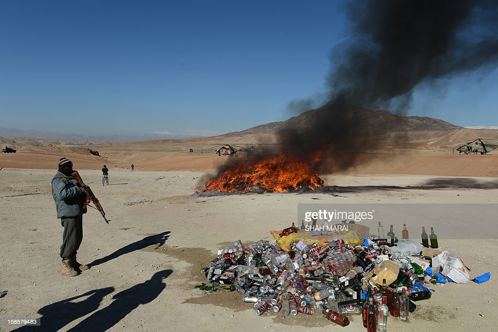 This photo taken on December 19, 2012 shows an Afghan policeman standing guard as a pile of narcotics (in background) is burned by officials on the outskirts of Jalalabad Nangarhar province. The United Nations said in November that opium poppy cultivation in Afghanistan has increased by 18 percent this year, sending a 'serious alarm signal' from the world's biggest opium producer. AFP PHOTO / SHAH Marai