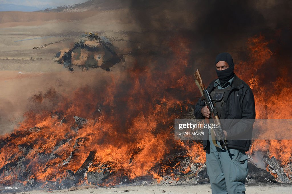 This photo taken on December 19, 2012 shows an Afghan policeman standing guard as a pile of narcotics is burned by officials on the outskirts of Jalalabad Nangarhar province. The United Nations said in November that opium poppy cultivation in Afghanistan has increased by 18 percent this year, sending a 'serious alarm signal' from the world's biggest opium producer. AFP PHOTO / SHAH Marai