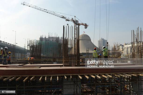 This photo taken on December 2 2016 shows labourers atop an underconstruction tower in the Bhendi Bazaar area in Mumbai that is being redeveloped...