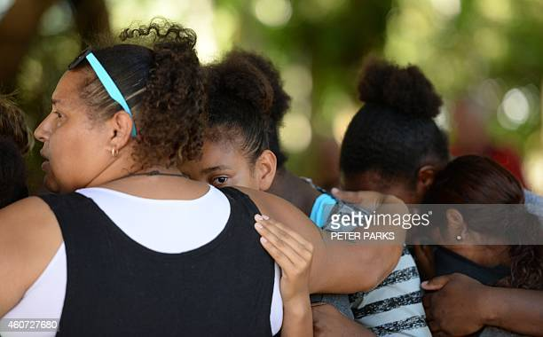 This photo taken on December 20 2014 shows people hugging at the scene where eight children ranging from babies to teenagers were found dead in a...