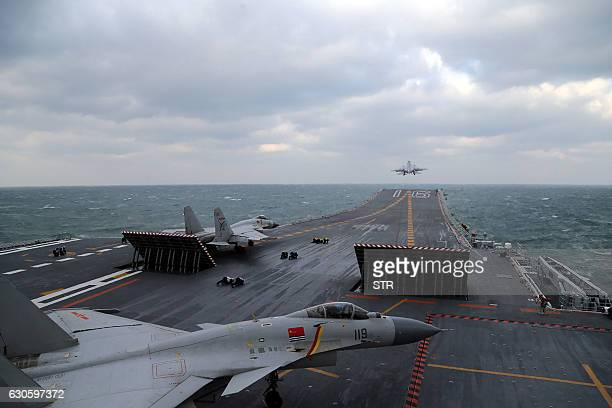 This photo taken on December 23 2016 shows Chinese J15 fighter jets being launched from the deck of the Liaoning aircraft carrier during military...