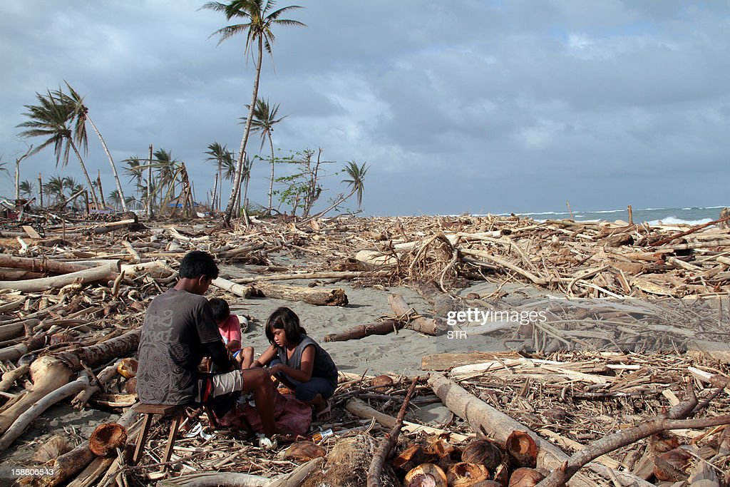This photo taken on December 29, 2012 shows a father and his children collecting coconuts among debris swept ashore at the height of Typhoon Bopha in Cateel in Davao Oriental province. The government is still feeding thousands of homeless survivors and building shelters for them after entire towns were wiped out by Bopha, the strongest typhoon to hit the country this year, as the death toll from a Tropical Storm Wukong that hit the central Philippines on Christmas Day rose to 20, with more than 20,000 others left homeless, the government said on December 30.