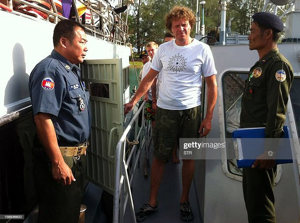This photo taken on December 30, 2012 shows Russian national Sergei Polonsky (C) being escorted by Cambodian military police officials from a boat at Sihanoukville, some 220 kilometers southwest of Phnom Penh. The real estate tycoon was among three Russian men arrested and charged in Cambodia over accusations they threatened and locked up the crew of a boat at knifepoint, an official said on January 4, 2013. The prosecutor at the Sihanoukville court said the men had been charged with intentional violence and illegal detention. AFP PHOTO