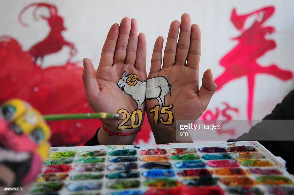 This photo taken on December 30 2014 shows a college student with paintings of a sheep on their hands to welcome the new year and to mark the coming...