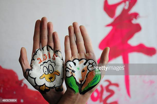 This photo taken on December 30 2014 shows college students with paintings of sheep on their hands to welcome the new year and to mark the coming...