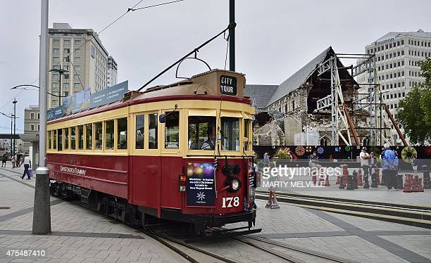 This photo taken on December 30 2014 shows the old trams working again next to Cathedral Square and the ruins of the old Christchurch Cathedral...