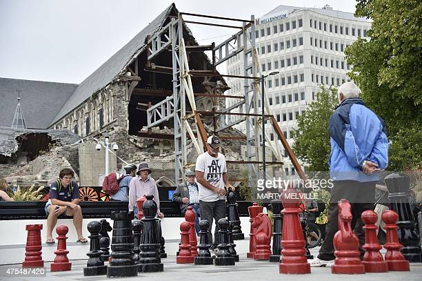 This photo taken on December 30 2014 shows two men playing a large game of chess in Cathedral Square next to the ruins of Christchurch Cathedral...