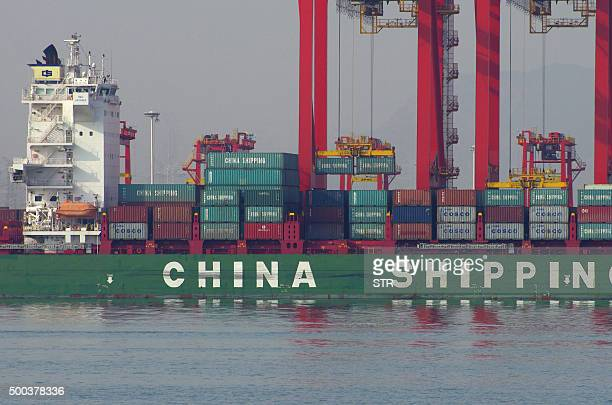 This photo taken on December 6 2015 shows containers being unloaded from a cargo ship at a port in Rizhao east China's Shandong province Chinese...
