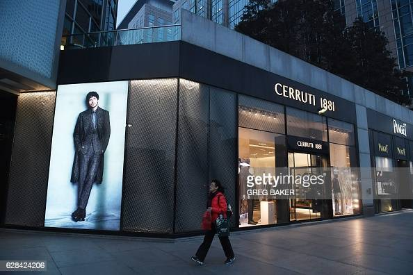This photo taken on December 7 2016 shows a woman walking past a fashion outlet at a shopping mall in Beijing China imports rose a forecastbeating 67...