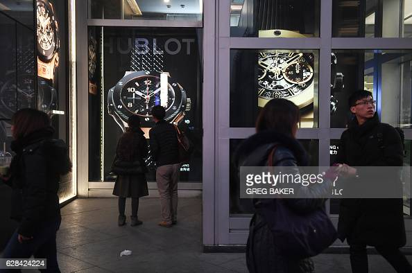 This photo taken on December 7 2016 shows people walking past a store selling imported watches at a shopping mall in Beijing China imports rose a...