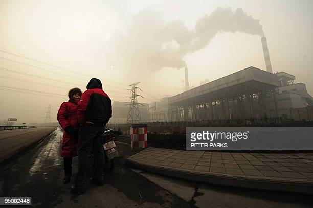 This photo taken on December 8 2009 shows two people talking outside a coal powered power plant on the outskirts of Linfen in China's Shanxi province...