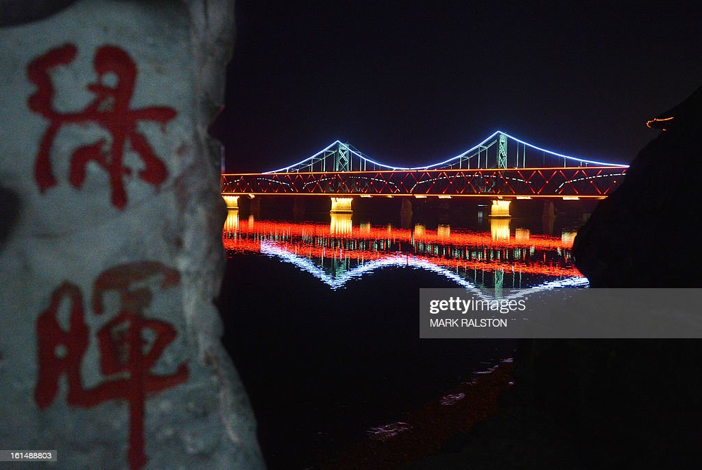 This photo taken on February 11, 2013 shows the Sino-Korean Friendship bridge taken from the Chinese town of Dandong and which ends in total darkness at the North Korean town of Sinuiju,. North Korean state media outlet has accused the US of 'jumping to conclusions' that the North would soon stage a nuclear test, adding to the confusion over its immediate intentions. The US and its ally South Korea are 'fussing over speculation' without knowing exactly what action the North plans to take, Tongil Sinbo, a Japan-based pro-North weekly magazine funded by Pyongyang, said. AFP PHOTO/Mark RALSTON