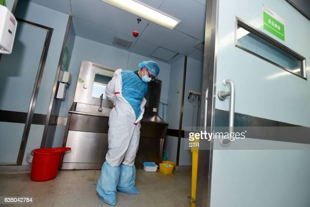 This photo taken on February 12 2017 shows a member of staff taking off his decontamination suit after treating a H7N9 bird flu patient in a hospital...