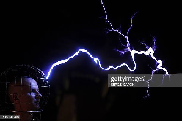 TOPSHOT This photo taken on February 13 2016 shows Oleg Melnik wearing a wire helmet getting electrical discharges of Tesla coil inside a Faraday...