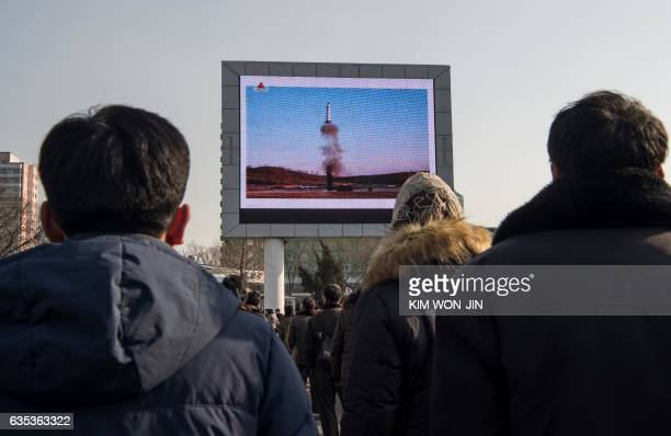 TOPSHOT This photo taken on February 13 2017 shows people in Pyongyang watching a public broadcast about the launch of a surfacetosurface medium...