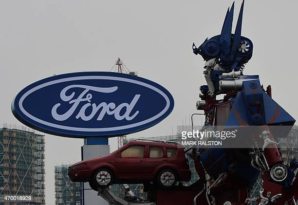 This photo taken on February 17 2014 shows a transformer robot advertising a Ford car dealership in Hangzhou Zhejiang Province Ford is catching up to...