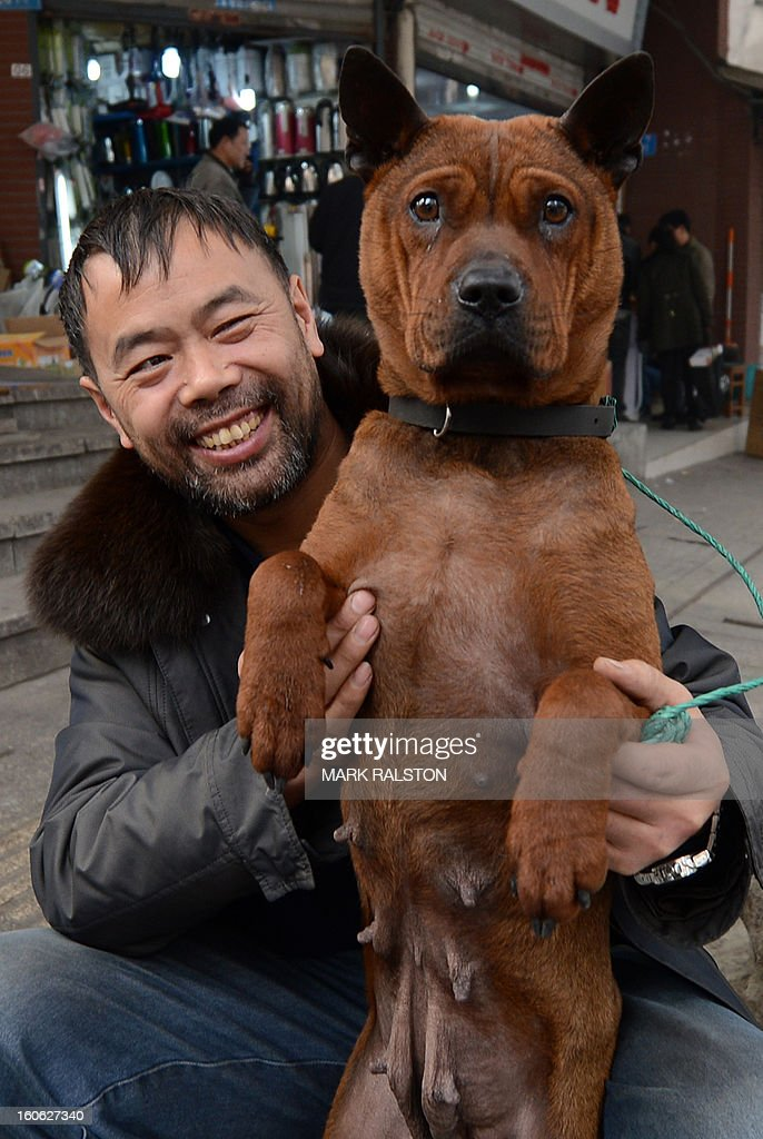 This photo taken on February 2, 2013 shows a Chinese dog breeder holding his dog for sale at a weekend pet market in Chongqing. Dog ownership is popular amongst China's elderly and the growing middle class but owners cannot keep dogs taller than 36 centimeters. AFP PHOTO/Mark RALSTON