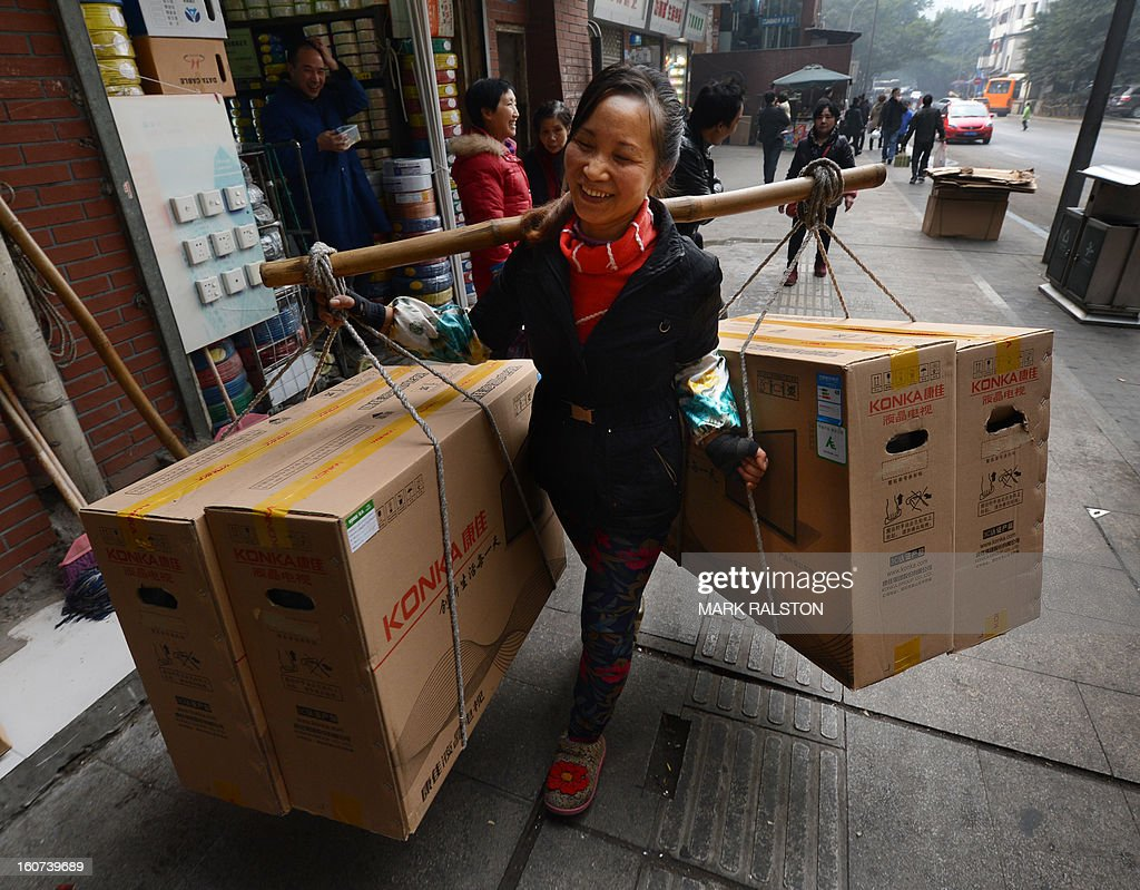 This photo taken on February 2, 2013 shows a Chinese woman known as a 'Bang Bang' carrying boxes on a bamboo pole in the Jiafeng Bei shopping area in Chongqing. Chinese state media has reported that Chongqing under the leadership of disgraced leader Bo Xilai raked up huge debts over his popularist transport infrastructure, social housing and construction projects. The reconstruction of the city of 32 million people however made Bo a popular figure amongst locals and made the Yangtze River city one of the world's fastest-growing urban areas. AFP PHOTO/Mark RALSTON