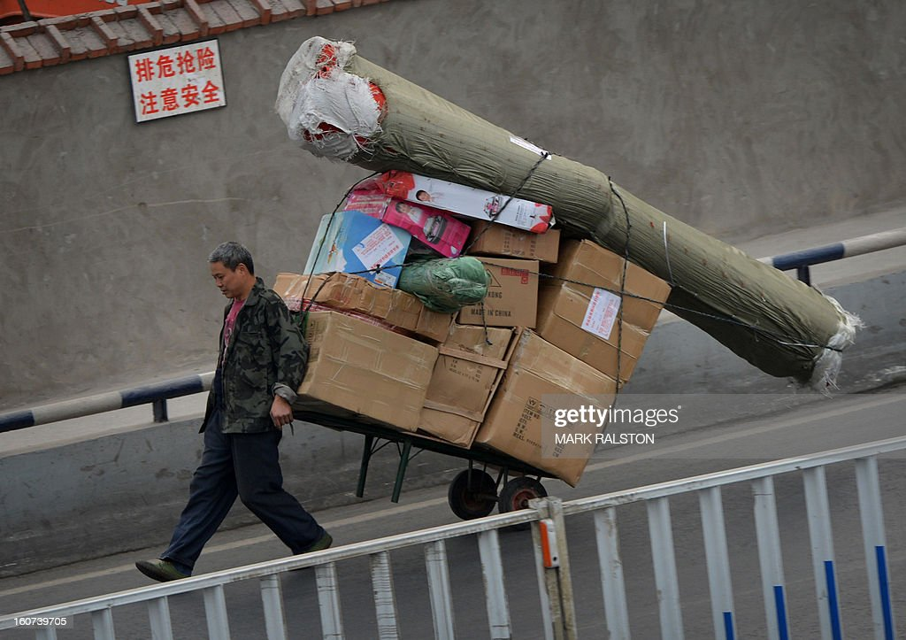 This photo taken on February 2, 2013 shows a Chinese worker moving boxes in the Jiafeng Bei shopping area in Chongqing. Chinese state media has reported that Chongqing under the leadership of disgraced leader Bo Xilai raked up huge debts over his popularist transport infrastructure, social housing and construction projects. The reconstruction of the city of 32 million people however made Bo a popular figure amongst locals and made the Yangtze River city one of the world's fastest-growing urban areas. AFP PHOTO/Mark RALSTON