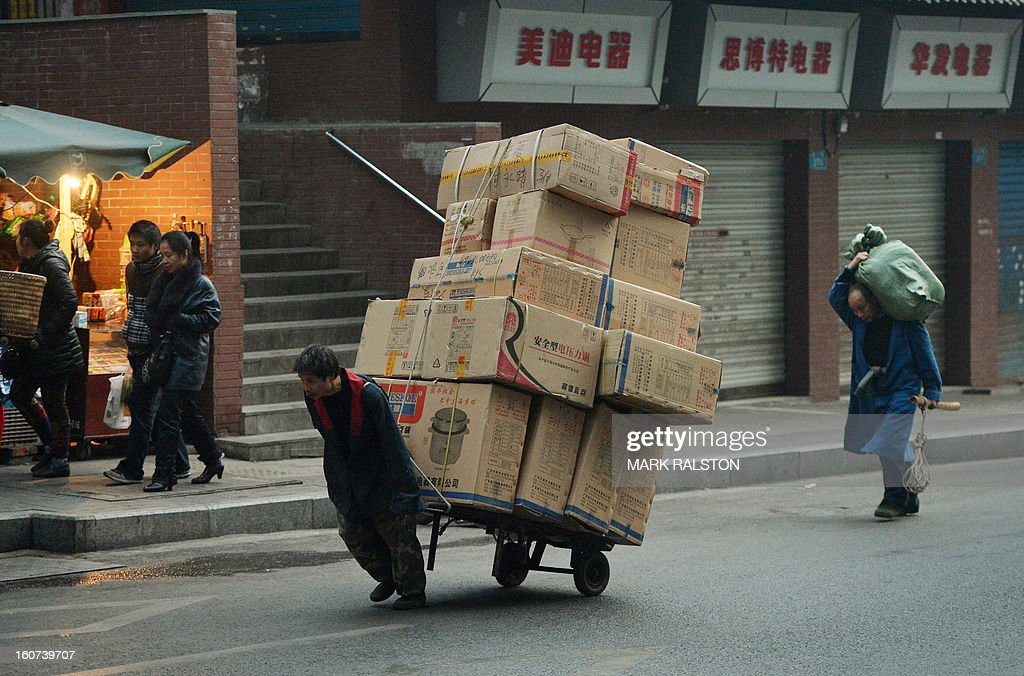 This photo taken on February 2, 2013 shows a Chinese worker pulling a large load of boxes in the Jiafeng Bei shopping area in Chongqing. Chinese state media has reported that Chongqing under the leadership of disgraced leader Bo Xilai raked up huge debts over his popularist transport infrastructure, social housing and construction projects. The reconstruction of the city of 32 million people however made Bo a popular figure amongst locals and made the Yangtze River city one of the world's fastest-growing urban areas. AFP PHOTO/Mark RALSTON