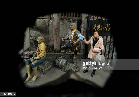 This photo taken on February 2 2013 shows a local residents posing for a photo beside a pirate display in Chongqing Chinese state media has reported...