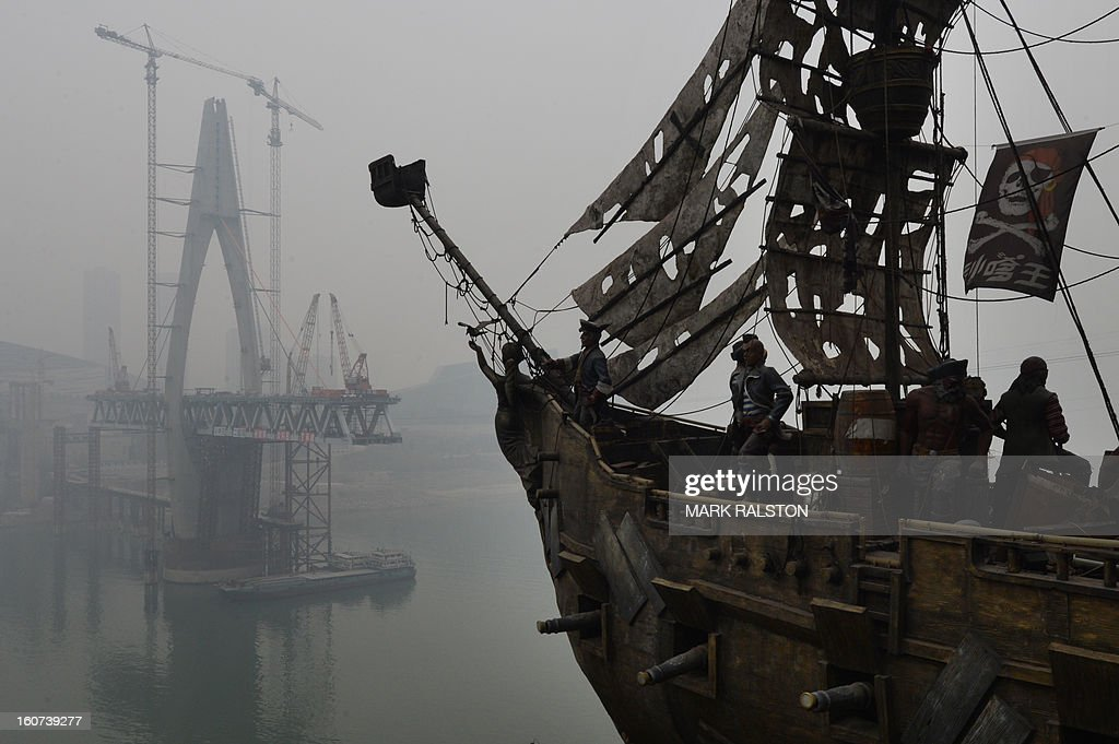 This photo taken on February 2, 2013 shows a pirate ship beside the construction site of the Qianximen Bridge which crosses the Jialing River in Chongqing. Chinese state media has reported that Chongqing under the leadership of disgraced leader Bo Xilai raked up huge debts over his popularist transport infrastructure, social housing and construction projects. The reconstruction of the city of 32 million people however made Bo a popular figure amongst locals and made the Yangtze River city one of the world's fastest-growing urban area's. AFP PHOTO/Mark RALSTON