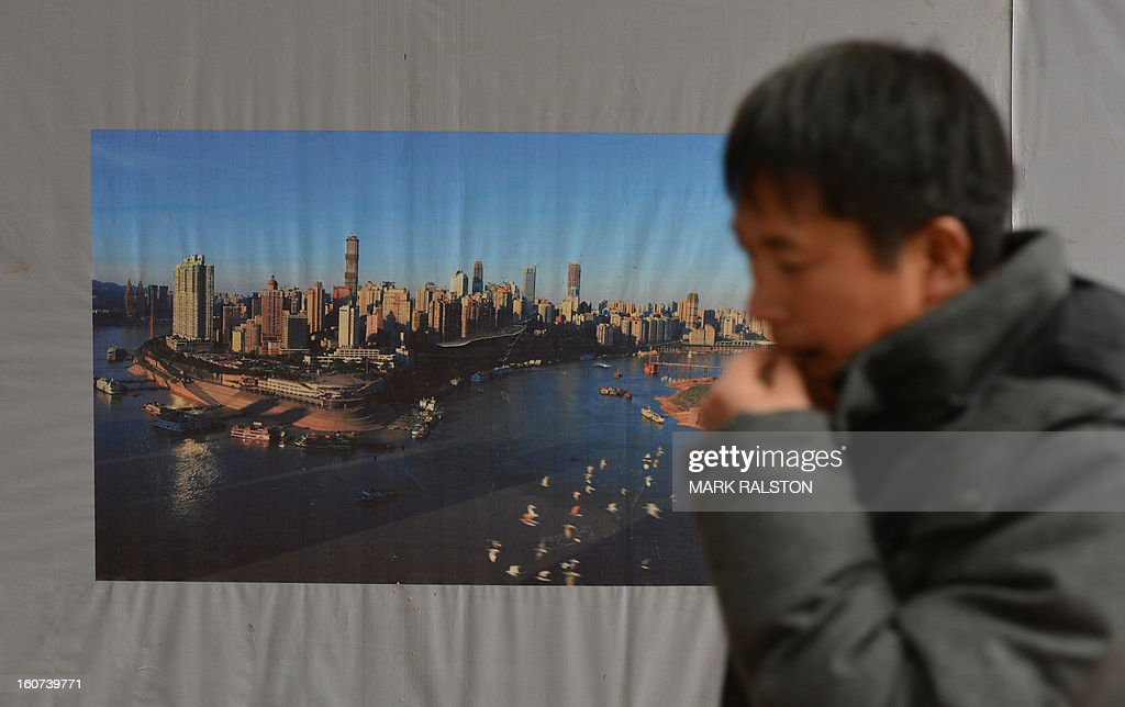 This photo taken on February 2, 2013 shows a worker leaving a construction site beside an image of developments in Chongqing. Chinese state media has reported that Chongqing under the leadership of disgraced leader Bo Xilai raked up huge debts over his popularist transport infrastructure, social housing and construction projects. The reconstruction of the city of 32 million people however made Bo a popular figure amongst locals and made the Yangtze River city one of the world's fastest-growing urban areas. AFP PHOTO/Mark RALSTON
