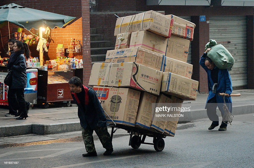 This photo taken on February 2, 2013 shows Chinese workers delivering electronic goods in the downtown shopping area of Chongqing. China said retail sales jumped nearly 15 percent on-year during the week-long Lunar New Year holiday, as consumers splurged on jewellery, clothes and food. Lunar New Year marks the biggest festival of the year in China as hundreds of millions of people journey across the country to celebrate the season with their families and consumer spending typically soars during the period. AFP PHOTO/Mark RALSTON