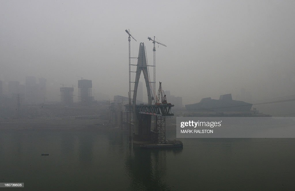 This photo taken on February 2, 2013 shows the new Qianximen Bridge and the Grand Theatre (R) from across the Jialing River in Chongqing. Chinese state media has reported that Chongqing under the leadership of disgraced leader Bo Xilai raked up huge debts over his popularist transport infrastructure, social housing and construction projects. The reconstruction of the city of 32 million people however made Bo a popular figure amongst locals and made the Yangtze River city one of the world's fastest-growing urban areas. AFP PHOTO/Mark RALSTON
