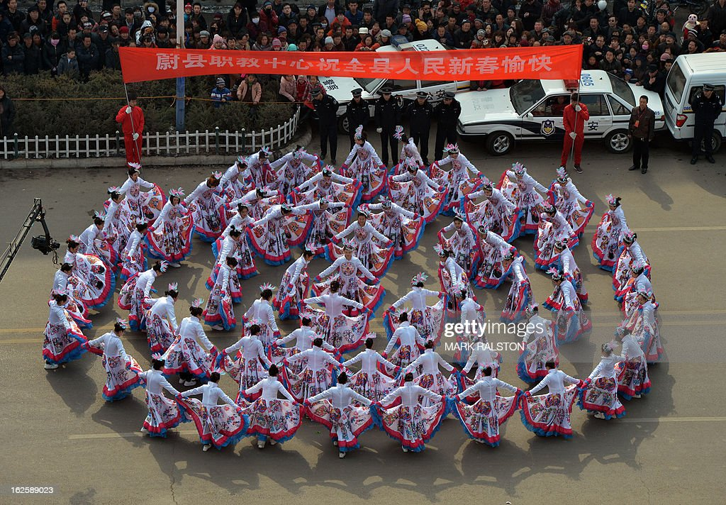 This photo taken on February 24, 2013 shows Chinese entertainers watched by a large crowd as they perform a dance during the traditional Lantern Festival parade which falls on the 15th day of the Lunar New Year, which officially ends its celebrations, in Yuxian. The festival which dates back more than 2000 years to the Han Dynasty sees China's cities become a sea of lanterns and fireworks. AFP PHOTO/Mark RALSTON
