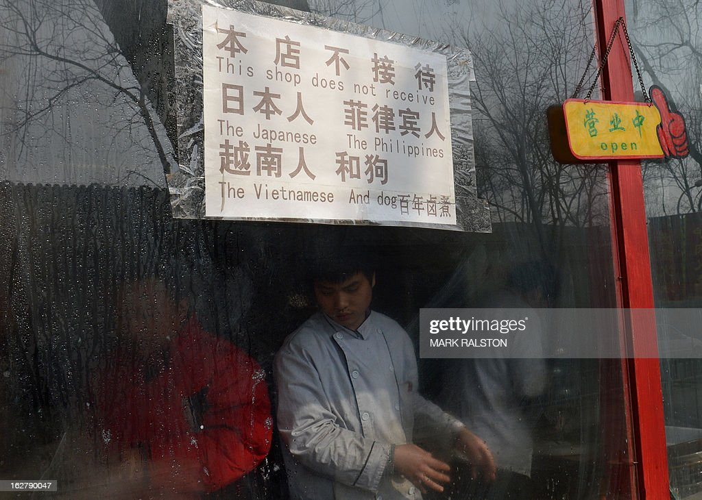 This photo taken on February 26, 2013 shows a Chinese cook working in a restaurant behind a sign that says 'This shop does not receive the Japanese, The Philippines, The Vietnamese and Dog' at the historic tourist district of Houhai in Beijing. A sign at a Beijing restaurant barring citizens of nations involved in maritime disputes with China -- along with dogs -- has triggered a wave of online outrage among Vietnamese and Filipinos. The Beijing Snacks restaurant near the Forbidden City, a popular tourist spot, has posted a sign on its door reading 'This shop does not receive the Japanese, the Philippines, the Vietnamese and dog(s).'Photographs of the controversial sign have gone viral in Vietnamese-language forums and featured heavily in Philippine newspapers and websites on February 27. AFP PHOTO/Mark RALSTON