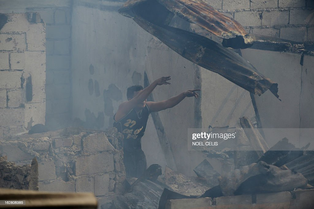 This photo taken on February 27, 2013 shows a resident clearing out a burnt out home to search for salvageable materials amongst destroyed houses after a fire engulfed a slum area in Manila. According to local reports, some 400 homes were destroyed leaving at least 500 families homeless.
