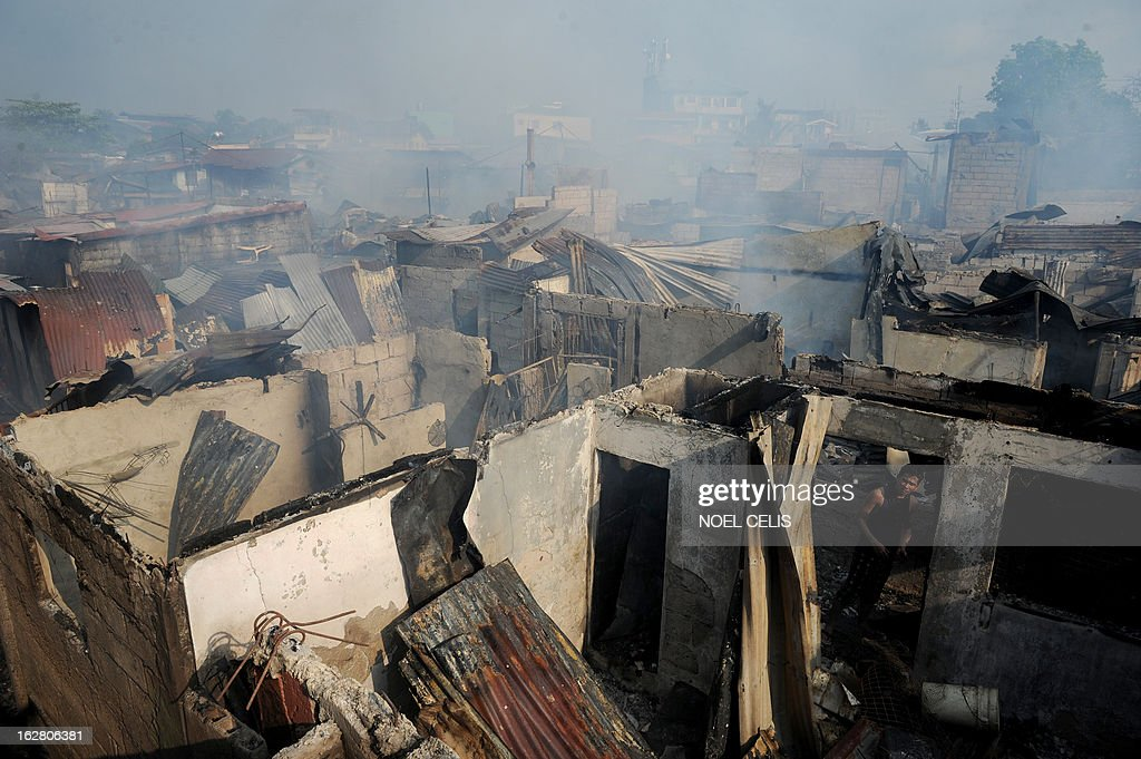 This photo taken on February 27, 2013 shows a resident (bottom R) looking at destroyed houses after a fire engulfed a slum area in Manila. According to local reports, some 400 homes were destroyed leaving at least 500 families homeless.