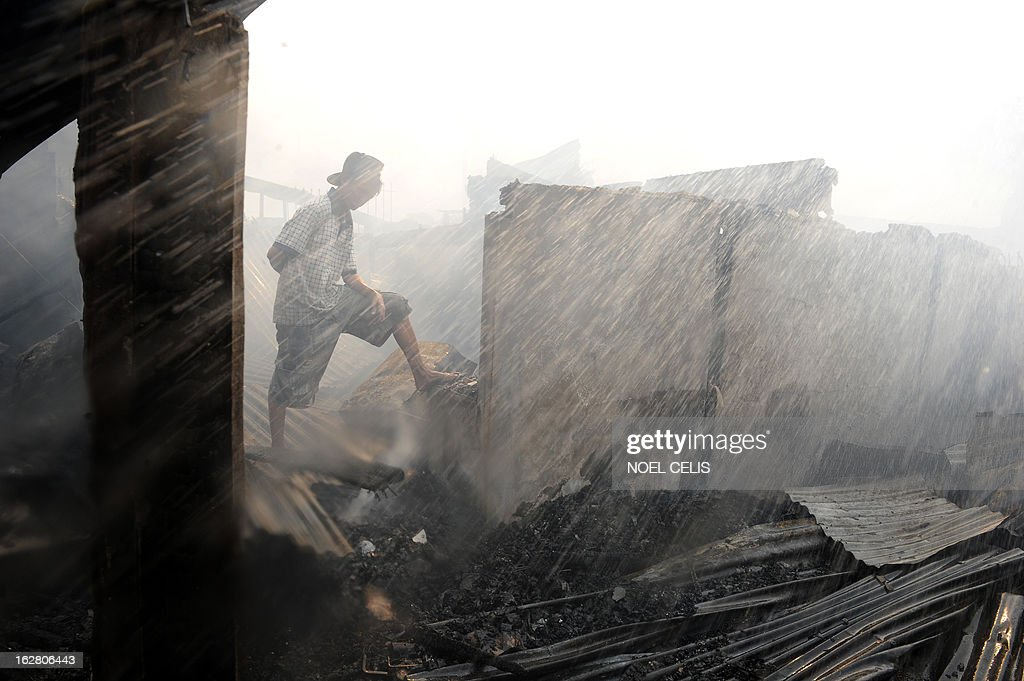 This photo taken on February 27, 2013 shows a resident looking at destroyed houses after a fire engulfed a slum area in Manila. According to local reports, some 400 homes were destroyed leaving at least 500 families homeless.