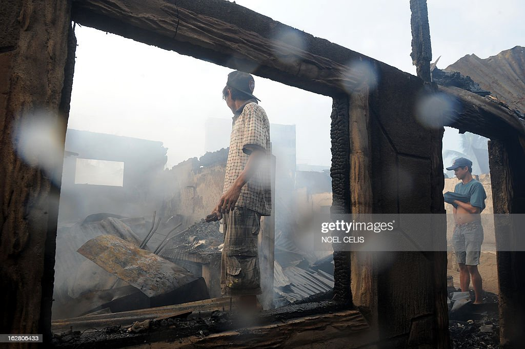 This photo taken on February 27, 2013 shows residents looking at destroyed houses after a fire engulfed a slum area in Manila. According to local reports, some 400 homes were destroyed leaving at least 500 families homeless.