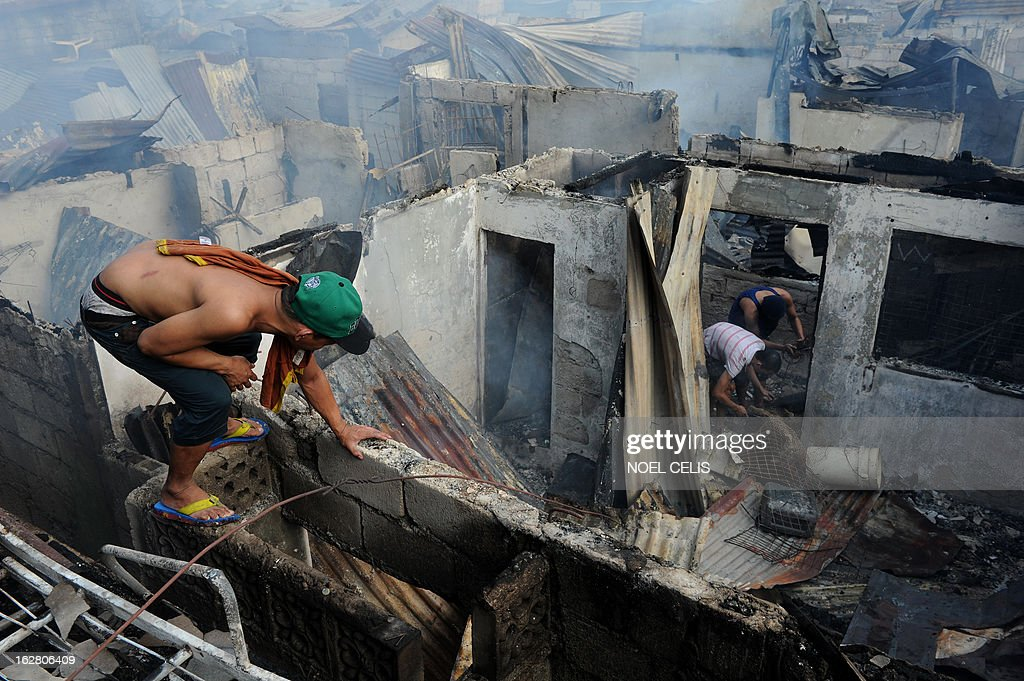 This photo taken on February 27, 2013 shows residents searching for salvageable materials amongst destroyed houses after a fire engulfed a slum area in Manila. According to local reports, some 400 homes were destroyed leaving at least 500 families homeless.