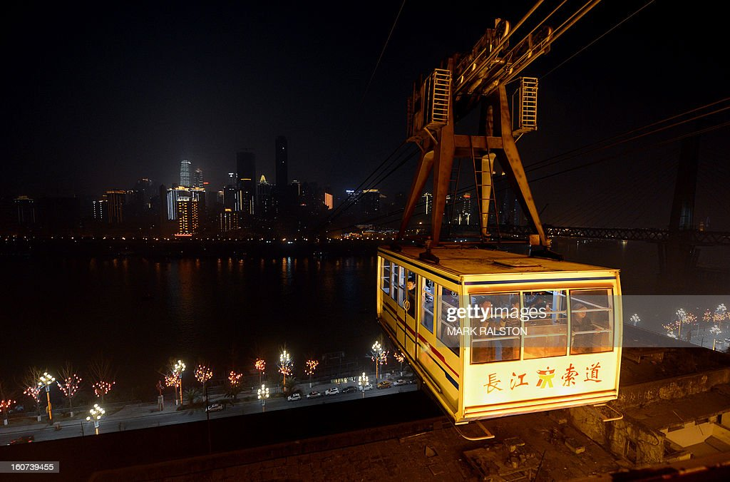 This photo taken on February 3, 2013 shows a cable car crossing the Yangtze River in Chongqing. Chinese state media has reported that Chongqing under the leadership of disgraced leader Bo Xilai raked up huge debts over his popularist transport infrastructure, social housing and construction projects. The reconstruction of the city of 32 million people however made Bo a popular figure amongst locals and made the Yangtze River city one of the world's fastest-growing urban areas. AFP PHOTO/Mark RALSTON