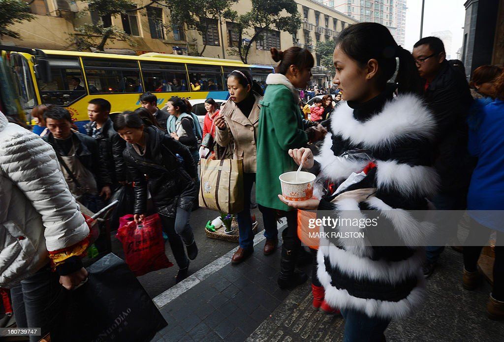 This photo taken on February 3, 2013 shows a colourfully dressed woman beside food stalls in the Jiafeng Bei shopping area in Chongqing. Chinese state media has reported that Chongqing under the leadership of disgraced leader Bo Xilai raked up huge debts over his popularist transport infrastructure, social housing and construction projects. The reconstruction of the city of 32 million people however made Bo a popular figure amongst locals and made the Yangtze River city one of the world's fastest-growing urban areas. AFP PHOTO/Mark RALSTON
