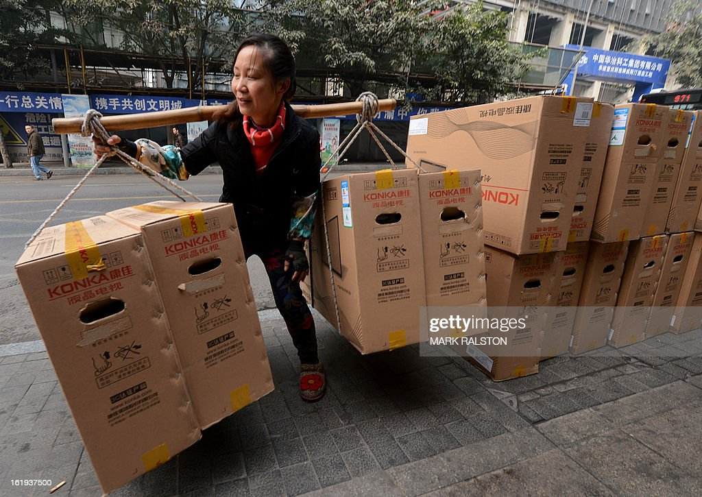 This photo taken on February 3, 2013 shows a female Chinese worker delivering flat screen televisions in the downtown shopping area of Chongqing. China said retail sales jumped nearly 15 percent on-year during the week-long Lunar New Year holiday, as consumers splurged on jewellery, clothes and food. Lunar New Year marks the biggest festival of the year in China as hundreds of millions of people journey across the country to celebrate the season with their families and consumer spending typically soars during the period. AFP PHOTO/Mark RALSTON