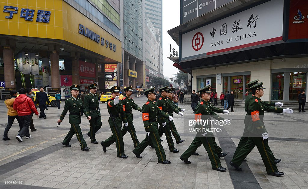 This photo taken on February 3, 2013 shows Chinese paramilitary police marching through the downtown area of Chongqing. Chinese state media has reported that Chongqing under the leadership of disgraced leader Bo Xilai raked up huge debts over his popularist transport infrastructure, social housing and construction projects. The reconstruction of the city of 32 million people however made Bo a popular figure amongst locals and made the Yangtze River city one of the world's fastest-growing urban areas. AFP PHOTO/Mark RALSTON