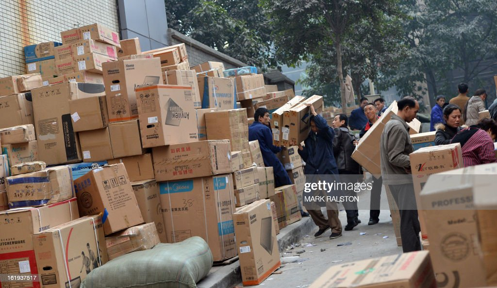 This photo taken on February 3, 2013 shows Chinese workers delivering flat screen televisions and electronic goods in the downtown shopping area of Chongqing. China said retail sales jumped nearly 15 percent on-year during the week-long Lunar New Year holiday, as consumers splurged on jewellery, clothes and food. Lunar New Year marks the biggest festival of the year in China as hundreds of millions of people journey across the country to celebrate the season with their families and consumer spending typically soars during the period. AFP PHOTO/Mark RALSTON