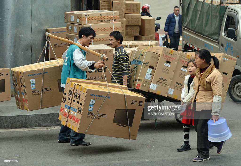 This photo taken on February 3, 2013 shows Chinese workers delivering flat screen televisions in the downtown shopping area of Chongqing. China said retail sales jumped nearly 15 percent on-year during the week-long Lunar New Year holiday, as consumers splurged on jewellery, clothes and food. Lunar New Year marks the biggest festival of the year in China as hundreds of millions of people journey across the country to celebrate the season with their families and consumer spending typically soars during the period. AFP PHOTO/Mark RALSTON