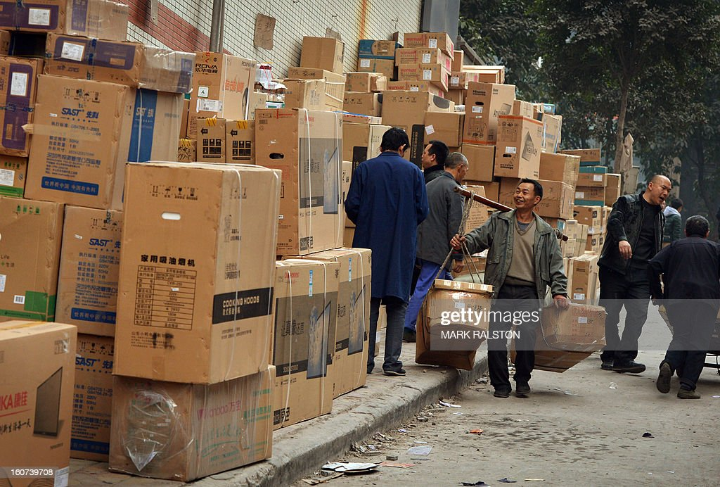 This photo taken on February 3, 2013 shows Chinese workers known as 'Bang Bang Men' carrying boxes on a bamboo pole in the Jiafeng Bei shopping area in Chongqing. Chinese state media has reported that Chongqing under the leadership of disgraced leader Bo Xilai raked up huge debts over his popularist transport infrastructure, social housing and construction projects. The reconstruction of the city of 32 million people however made Bo a popular figure amongst locals and made the Yangtze River city one of the world's fastest-growing urban areas. AFP PHOTO/Mark RALSTON