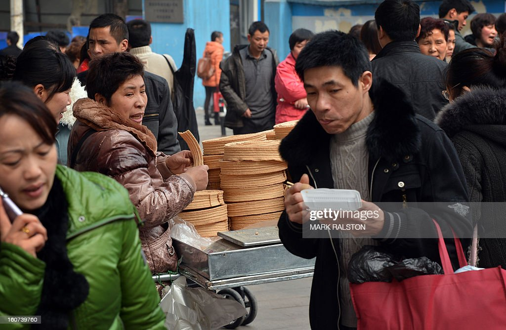 This photo taken on February 3, 2013 shows customers visiting the food stalls in the Jiafeng Bei shopping area in Chongqing. Chinese state media has reported that Chongqing under the leadership of disgraced leader Bo Xilai raked up huge debts over his popularist transport infrastructure, social housing and construction projects. The reconstruction of the city of 32 million people however made Bo a popular figure amongst locals and made the Yangtze River city one of the world's fastest-growing urban areas. AFP PHOTO/Mark RALSTON