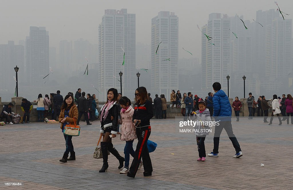 This photo taken on February 3, 2013 shows local residents at the Chaotianmen Park in front of a newly completed social housing project in Chongqing. Chinese state media has reported that Chongqing under the leadership of disgraced leader Bo Xilai raked up huge debts over his popularist transport infrastructure, social housing and construction projects. The reconstruction of the city of 32 million people however made Bo a popular figure amongst locals and made the Yangtze River city one of the world's fastest-growing urban areas. AFP PHOTO/Mark RALSTON