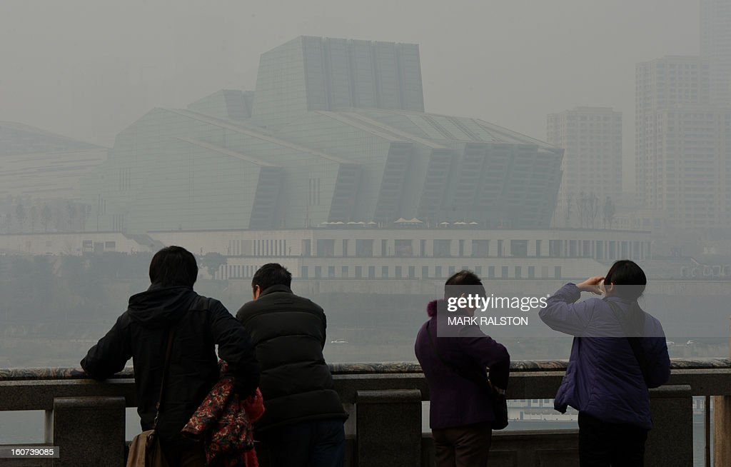 This photo taken on February 3, 2013 shows local residents viewing the new Grand Theatre from across the Jialing River in Chongqing. Chinese state media has reported that Chongqing under the leadership of disgraced leader Bo Xilai raked up huge debts over his popularist transport infrastructure, social housing and construction projects. The reconstruction of the city of 32 million people however made Bo a popular figure amongst locals and made the Yangtze River city one of the world's fastest-growing urban area's. AFP PHOTO/Mark RALSTON