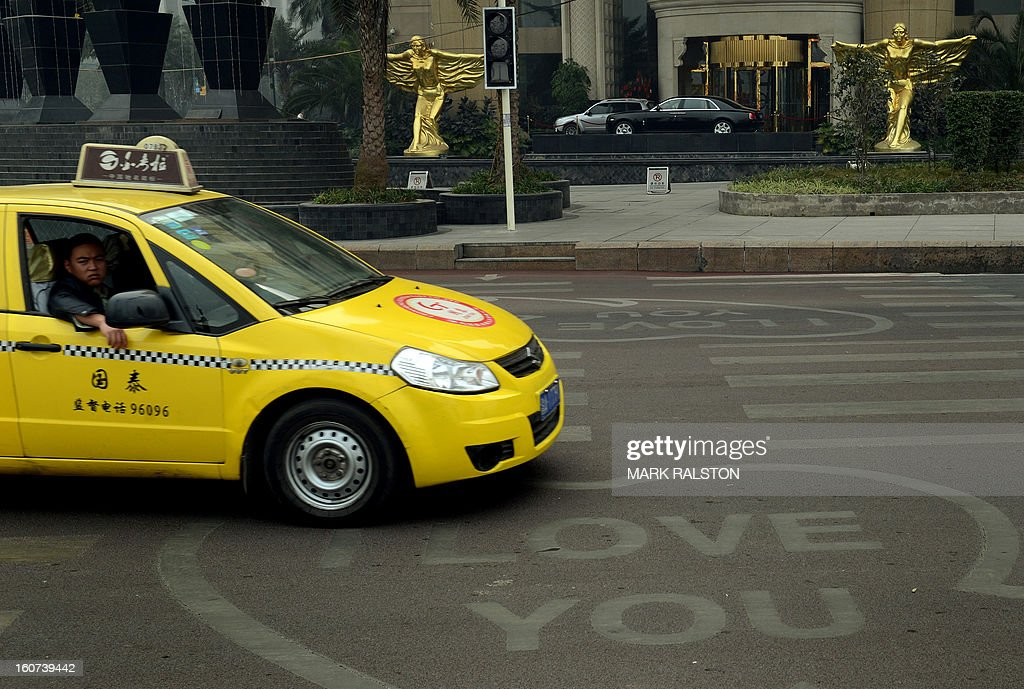 This photo taken on February 4, 2013 shows a taxi passing by 'I Love You' signs on a road crossing outside a hotel in the Nan'an district which was an area politically loyal to Bo Xilai and one of the two hotels where murdered British businessman Neil Heywood stayed at during his last week alive in Chongqing. Chinese state media has reported that Chongqing under the leadership of disgraced leader Bo Xilai raked up huge debts over his popularist transport infrastructure, social housing and construction projects. The reconstruction of the city of 32 million people however made Bo a popular figure amongst locals and made the Yangtze River city one of the world's fastest-growing urban areas. AFP PHOTO/Mark RALSTON