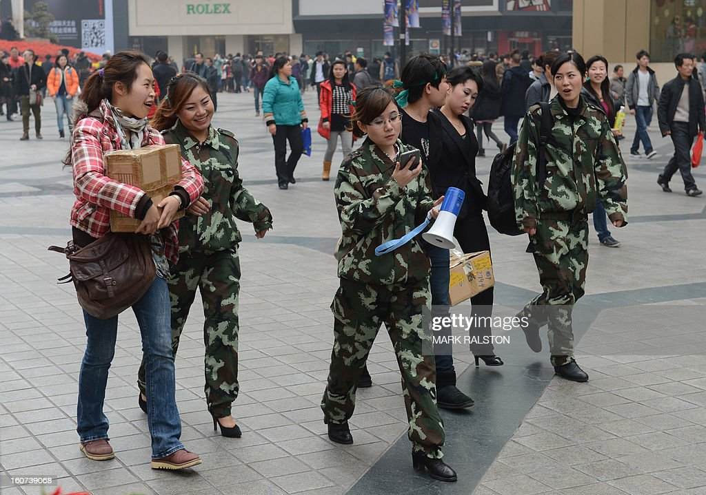 This photo taken on February 4, 2013 shows uniformed Chinese women walking through the downtown area of Chongqing after the recent announcement that the special female police squads set up by Bo Xilai would be disbanded. Chinese state media has reported that Chongqing under the leadership of disgraced leader Bo Xilai raked up huge debts over his popularist transport infrastructure, social housing and construction projects. The reconstruction of the city of 32 million people however made Bo a popular figure amongst locals and made the Yangtze River city one of the world's fastest-growing urban area's. AFP PHOTO/Mark RALSTON