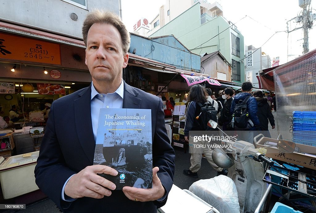 This photo taken on February 5, 2013 shows Patrick Ramage, global whale programme director of the International Fund for Animal Welfare (IFAW), holding a report on the economics of Japan's whaling industry outside Tsukiji Market, Japan's biggest fish market, in Tokyo. Japan's whaling programme costs taxpayers 10 million USD a year, the pressure group said on February 5, as it demanded an end to the 'dying industry'. AFP PHOTO / Toru YAMANAKA